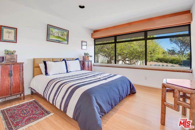 Các tác phẩm nghệ thuật đóng khung màu đỏ thêm một điểm nhấn đẹp trong Phòng ngủ phong cách nội thất chiết trung này trưng bày các đầu giường mộc mạc và một chiếc giường búi màu be mặc trên giường sọc trắng và xanh. Nó được bổ sung bởi một tấm thảm tua rua và một chiếc bàn hình lục giác hòa quyện với sàn gỗ cứng mịn.