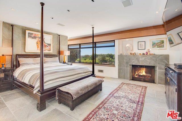 Phòng ngủ phong cách nội thất chiết trung này có một chiếc giường bốn cọc với một chiếc ghế bành ở cuối cùng với một người chạy màu đỏ nằm trên sàn lát gạch bê tông kéo dài đến bao quanh lò sưởi và phông nền của giường.