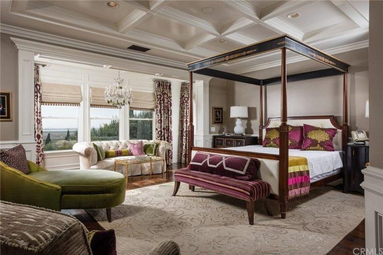Phòng ngủ phong cách nội thất chiết trung rộng lớn với trần nhà và sàn gỗ cứng được phủ bởi một tấm thảm họa tiết hoa. Nó được trang bị với nhiều chỗ ngồi theo phong cách khác nhau và một chiếc giường tán bên cạnh đầu giường bằng gỗ tối màu chống lại wainscote trắng.