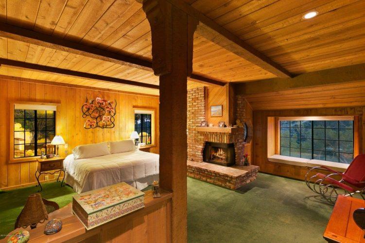 Ánh sáng xung quanh từ đèn bàn và lò sưởi bằng gạch tạo cảm giác ấm áp và ấm cúng trong Phòng ngủ phong cách nội thất chiết trung này với sàn trải thảm màu xanh lá cây và tường ván gỗ kéo dài đến trần nhà bằng gỗ.