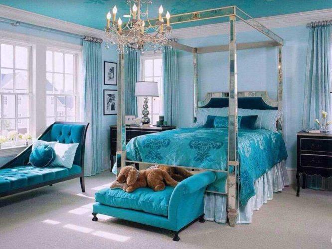 Phòng ngủ chính theo phong cách chiết trung tự hào với một chiếc giường và ghế màu xanh tuyệt đẹp, cùng với trần nhà màu xanh trang trí được thắp sáng bởi một chiếc đèn chùm lộng lẫy.