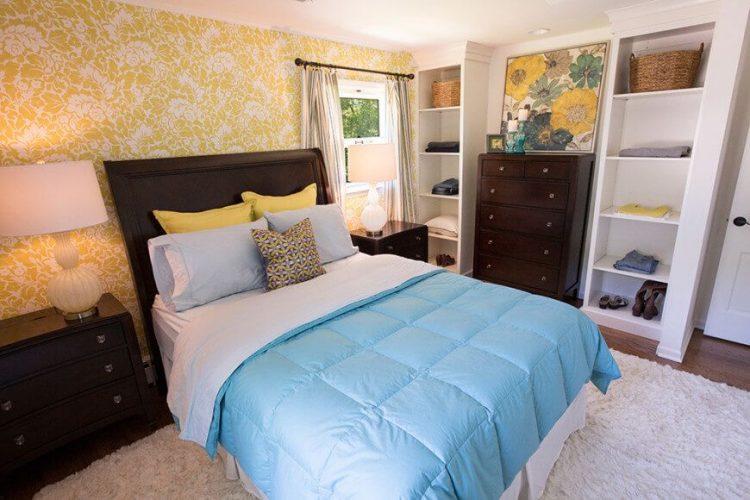 Một shot tập trung vào thiết lập giường quyến rũ của phòng ngủ này. Phòng có những bức tường màu vàng trang nhã và hai bàn cạnh giường ngủ, cùng với kệ tích hợp.