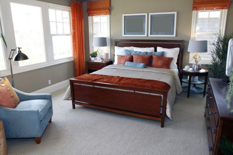 Phòng ngủ chính có thảm trải sàn màu xám và tường màu xám. Nó cung cấp một thiết lập giường sang trọng được thắp sáng bởi đèn bàn màu xám trên đầu bàn cạnh giường ngủ.