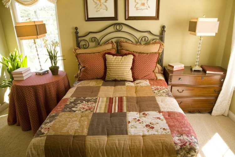 Một cái nhìn cận cảnh về bộ giường sang trọng của phòng ngủ chính này được thắp sáng bởi những chiếc đèn bàn sành điệu ở hai bên. Căn phòng được bao quanh bởi những bức tường màu nâu.