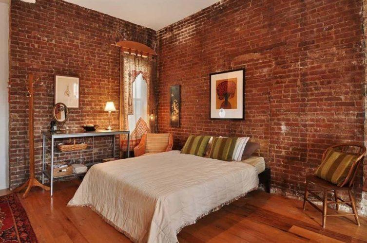 Phòng ngủ phong cách nội thất chiết trung có tường gạch đỏ và sàn gỗ cứng. Nó cung cấp một thiết lập giường đẹp với hai ghế ở hai bên.
