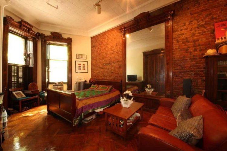 Phòng ngủ chính này có một bức tường gạch đỏ và trần nhà cao với đèn theo dõi. Phòng có một chiếc giường mộc mạc cùng với một chiếc ghế da lớn màu nâu ở bên cạnh.