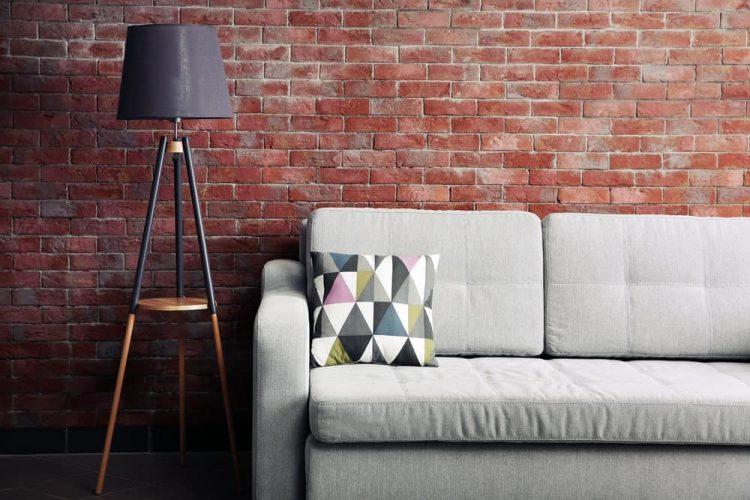 Đèn sàn bên cạnh ghế sofa trong phòng có tường gạch.