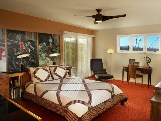 Phòng ngủ chính này tự hào trang trí tường nghệ thuật trên bức tường màu cam của phòng. Nó có một thiết lập giường vừa phải được thắp sáng bởi đèn bàn thời trang.