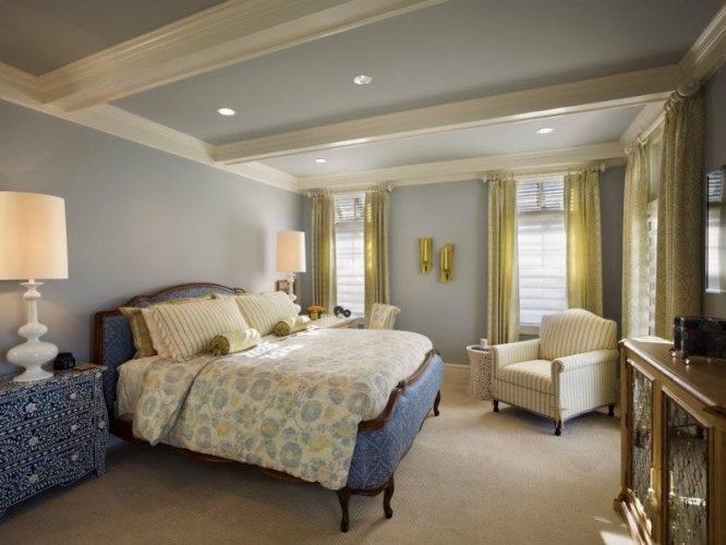 Phòng ngủ chính chiết trung tự hào với một thiết lập giường lớn thanh lịch được thắp sáng bởi đèn bàn lớn sang trọng ở cả hai bên. Phòng có tường và trần màu xám xanh, cùng với sàn trải thảm.