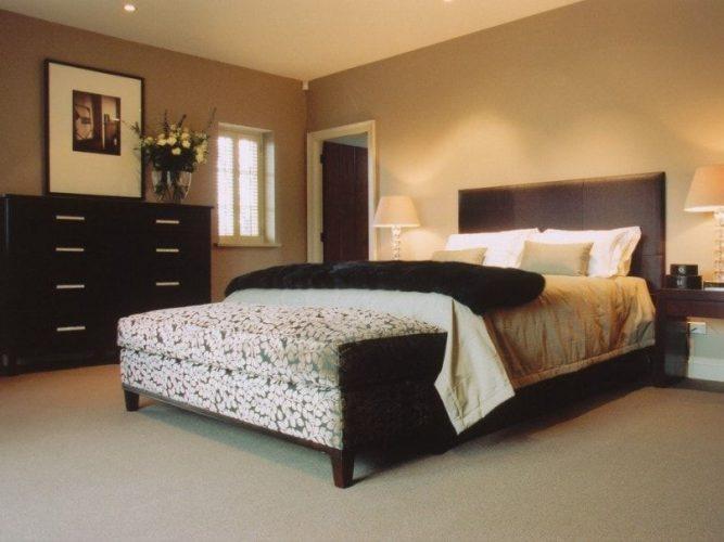 Một bức ảnh tập trung vào chiếc giường sang trọng của phòng ngủ chính này được chiếu sáng bằng đèn bàn ở cả hai bên, được bao quanh bởi những bức tường màu nâu và sàn trải thảm.