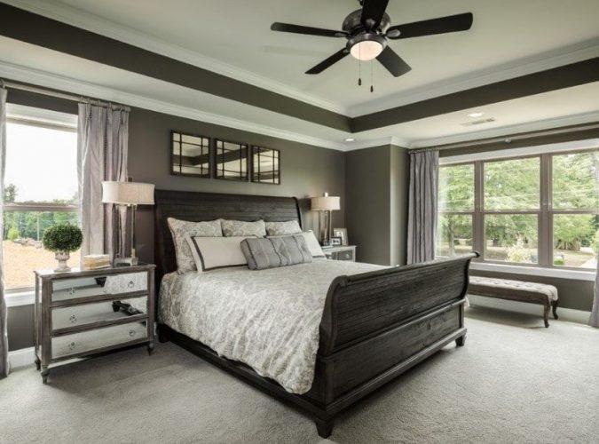 Một bức ảnh tập trung vào thiết lập giường sang trọng của phòng ngủ chính này được chiếu sáng bằng đèn bàn ở cả hai bên, được bao quanh bởi những bức tường màu đen và cửa sổ kính.