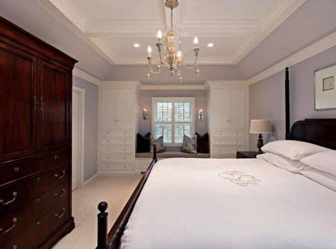 Phòng ngủ chính nổi bật với những bức tường màu xám nhạt và trần nhà tuyệt đẹp được thắp sáng bởi một chiếc đèn chùm quyến rũ. Phòng có giường thoải mái và tủ quần áo có ngăn kéo.