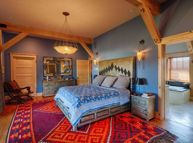 Một phòng ngủ chính rộng rãi với một chiếc giường lớn trên một tấm thảm phong cách lớn bao phủ sàn gỗ cứng. Phòng có tường màu xanh và có phòng tắm riêng.