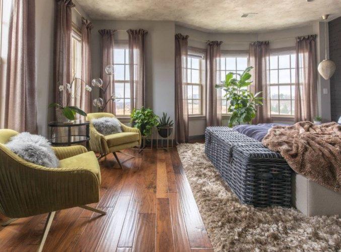 Phòng ngủ chính lớn chiết trung với những bức tường màu xám, sàn gỗ cứng và trần nhà tuyệt đẹp. Phòng có một chiếc giường ấm cúng đặt trên một tấm thảm lớn.