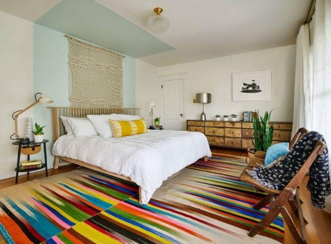 Phòng ngủ chính chiết trung tự hào với một tấm thảm phong cách và đầy màu sắc bao phủ sàn gỗ cứng. Phòng có một chiếc giường lớn và một bàn bên mộc mạc.