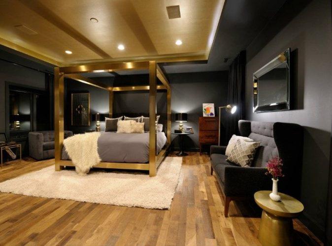 Phòng ngủ chính kiểu Eclectic này tự hào có một chiếc giường sang trọng được bao quanh bởi những bức tường màu đen. Phòng có trần khay tuyệt đẹp và sàn gỗ cứng.
