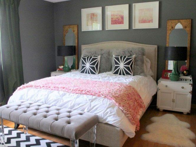 Một cái nhìn cận cảnh về thiết lập giường hiện đại của phòng ngủ chính này được chiếu sáng bởi một cặp đèn bàn màu đen, được bao quanh bởi những bức tường màu xám.
