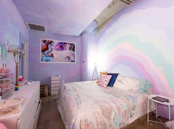 Phòng ngủ của một cô gái tự hào với những bức tường màu tím với một trang trí nghệ thuật treo tường trừu tượng. Phòng có giường thoải mái và bàn bên màu trắng.