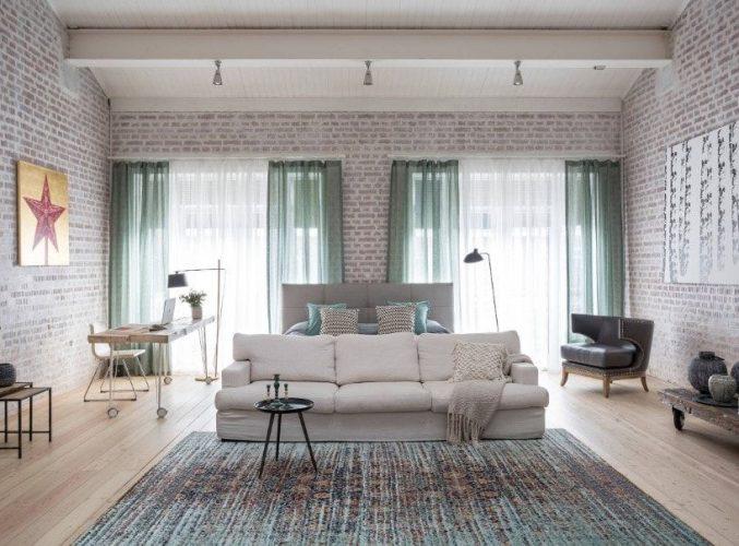 Một phòng ngủ chính rộng rãi chiết trung với những bức tường gạch và trần nhà cao, cùng với sàn gỗ cứng được phủ bởi một tấm thảm khu vực. Phòng có một chiếc giường màu xám hiện đại cùng với bàn học ở bên cạnh.