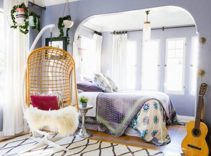Phòng ngủ chính kiểu Eclectic này có thiết lập giường ấm cúng được bao quanh bởi những bức tường màu tím. Phòng có sàn gỗ cứng đứng đầu bởi một tấm thảm khu vực.