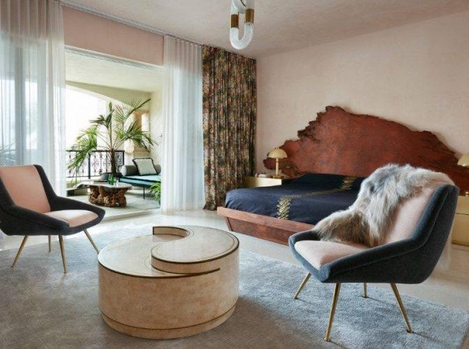 Phòng ngủ chính rộng rãi có thiết lập giường lớn tuyệt đẹp cùng với hai chiếc ghế hiện đại với bàn trung tâm đầy phong cách trên tấm thảm màu xám.