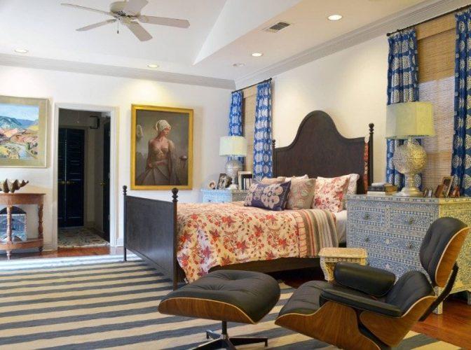 Một phòng ngủ chính rộng rãi tự hào với một chiếc giường thanh lịch được thắp sáng bởi đèn bàn ở cả hai bên, cùng với nhiều mảng tường nghệ thuật trên các bức tường trắng.