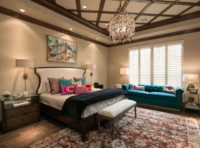Phòng ngủ chính này tự hào có một đèn chùm quyến rũ treo trên trần khay với thiết kế tráng lệ. Phòng có một chiếc giường lớn ấm cúng cùng với một chiếc ghế dài màu xanh thanh lịch ở bên cạnh.
