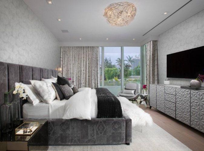 Phòng ngủ chính với những bức tường đầy phong cách và sàn gỗ cứng. Căn phòng tự hào có một chiếc giường màu xám sang trọng được đặt cùng với một TV màn hình rộng đặt trước giường.