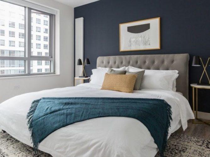 Một cái nhìn tập trung vào chiếc giường hiện đại lớn của phòng ngủ chính này với đèn bàn phong cách ở cả hai bên. Căn phòng có một bức tường màu trắng và xám đen, cùng với các cửa sổ bằng kính.
