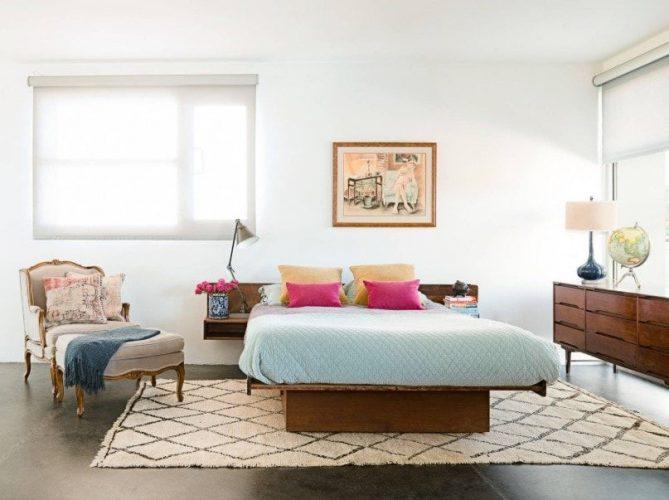 Phòng ngủ chính có giường ấm cúng với bàn phụ tích hợp. Phòng có tường và trần màu trắng, cùng với sàn gỗ cứng.
