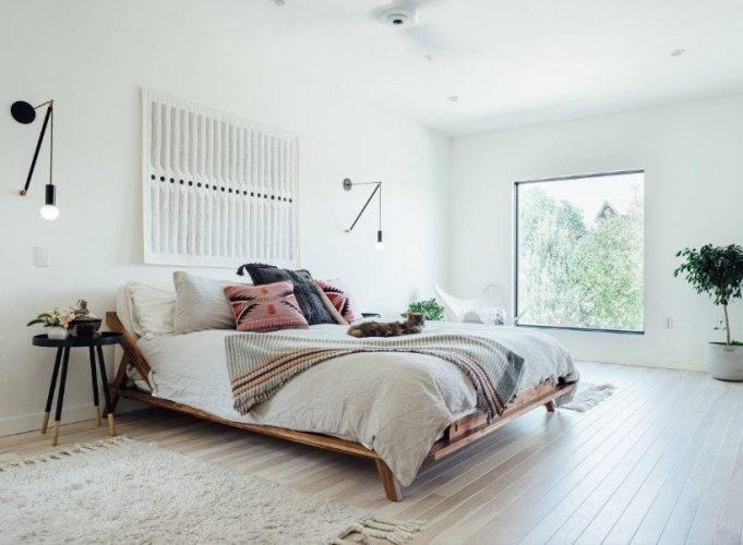 Phòng ngủ chính rộng rãi chiết trung với những bức tường trắng và trần nhà màu trắng, cùng với sàn gỗ cứng. Phòng cung cấp một thiết lập giường lớn được thắp sáng bởi đèn tường phong cách.