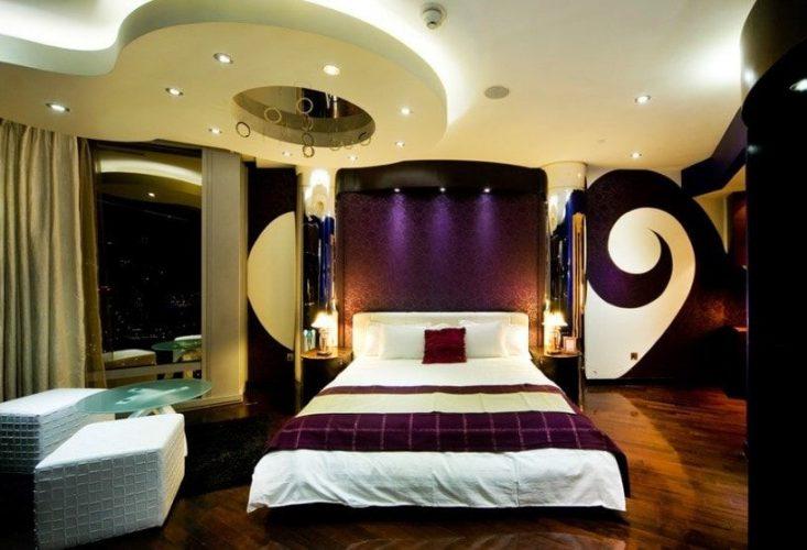 Một phòng ngủ chính quyến rũ tự hào với trần tùy chỉnh tuyệt đẹp và các thiết kế tường đầy phong cách, cùng với sàn gỗ cứng và cửa sổ kính. Phòng cung cấp một thiết lập giường sang trọng cùng với một cặp ghế màu trắng ở bên cạnh với một bàn trung tâm bằng kính.