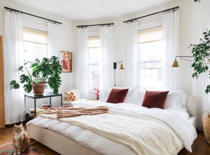 Một bức ảnh tập trung vào chiếc giường thoải mái lớn của phòng ngủ này được bao quanh bởi những bức tường trắng và rèm cửa sổ màu trắng đáng yêu.