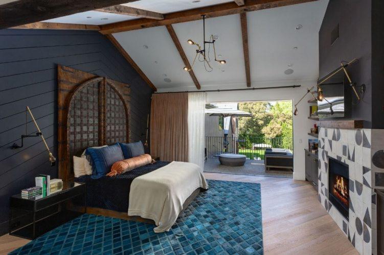 Phòng ngủ chính quyến rũ có những bức tường màu đen tuyệt đẹp được bổ sung bởi trần nhà thờ trắng với những dầm lộ ra.  Bên kia giường là một lò sưởi hiện đại được dát trong một bức tường đen trắng.