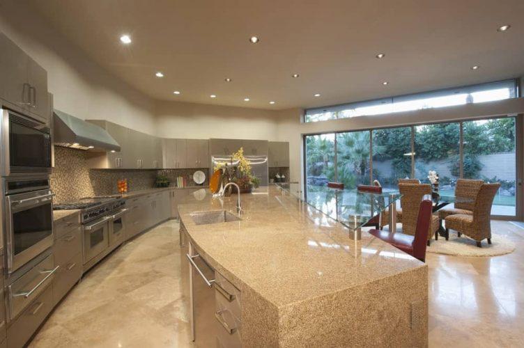 Nhà bếp mở với đèn chiếu sáng, thiết bị bằng thép không gỉ và một hòn đảo.