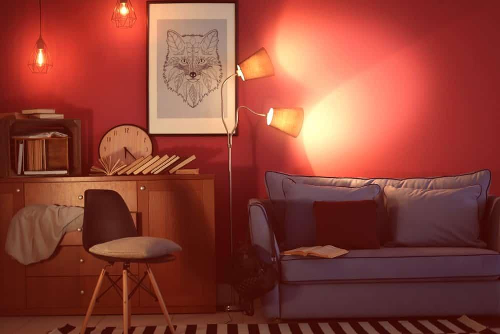 Văn phòng và phòng khách theo phong cách retro với những bức tường màu hồng, nghệ thuật đóng khung, đèn treo cổ điển, đèn sàn và ghế sofa.