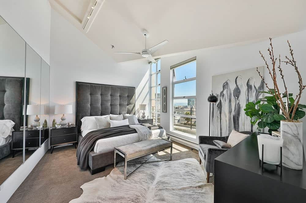 Phòng ngủ chính đáng yêu này có một chiếc giường bục màu đen với đầu giường lớn và có đệm để nổi bật trên những bức tường trắng sáng và trần nhà màu trắng.  Chiếc giường phù hợp với ghế bành và tủ quần áo ở phía bên kia của căn phòng cũng như các ngăn kéo đầu giường.