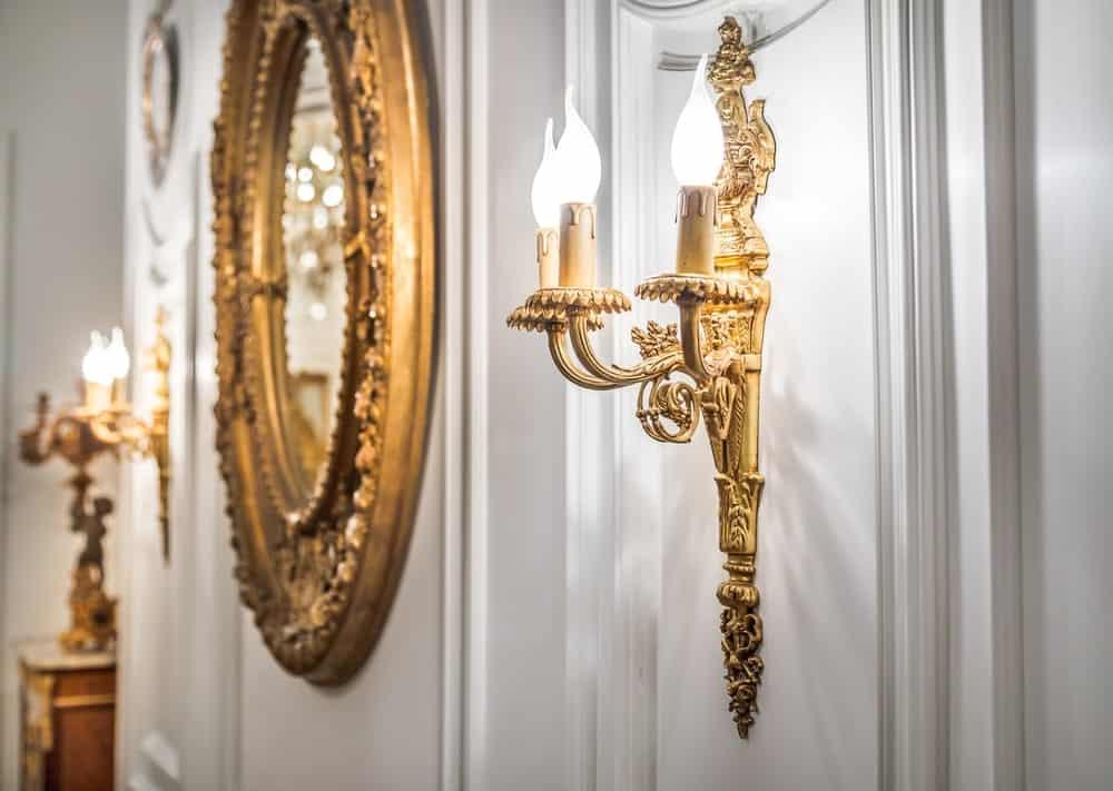 Gương hình bầu dục mạ vàng nằm giữa một cặp sconces tường kiểu mạ vàng.