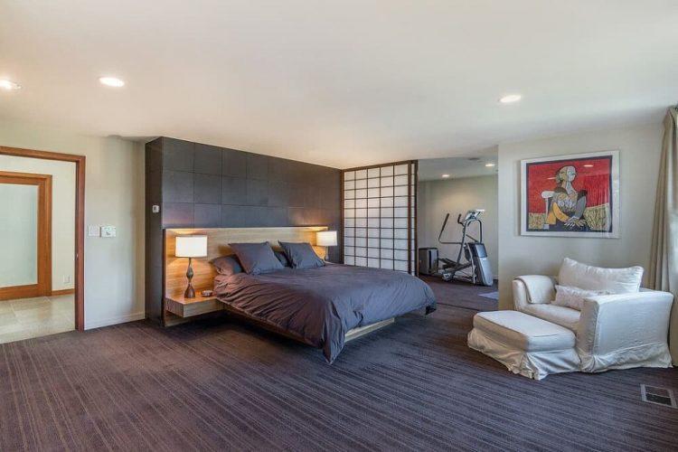 Đây là một phòng ngủ chính rộng rãi với sàn trải thảm màu đen để phù hợp với các tấm, gối và tường màu đen phía sau giường. Những thứ này sau đó được bổ sung bởi trần nhà màu trắng, tường và ghế bành có đệm.