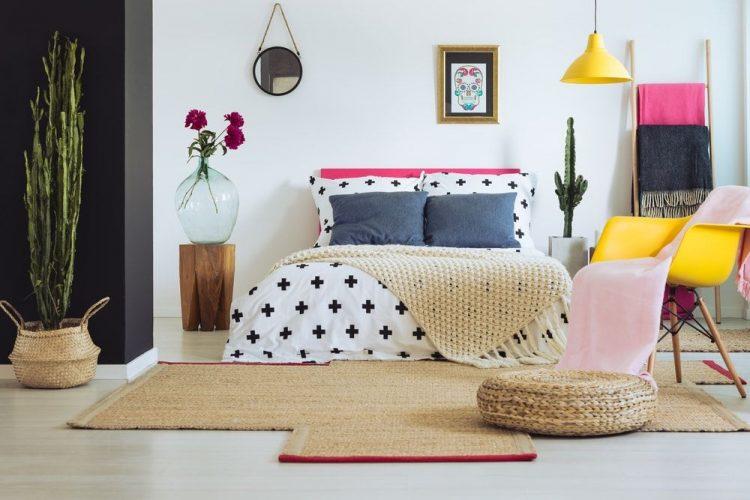 Một cái nhìn tập trung vào thiết lập giường đáng yêu của phòng ngủ chính Eclectic này được chiếu sáng bởi một ánh sáng mặt dây chuyền màu vàng phù hợp với chiếc ghế ngồi màu vàng ở bên cạnh.