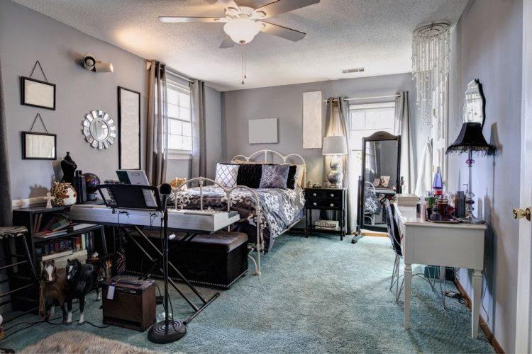 Phòng ngủ chính lớn Eclectic với thảm trải sàn và tường màu xám nhạt. Phòng có giường sang trọng và kiểu dáng tường hấp dẫn.