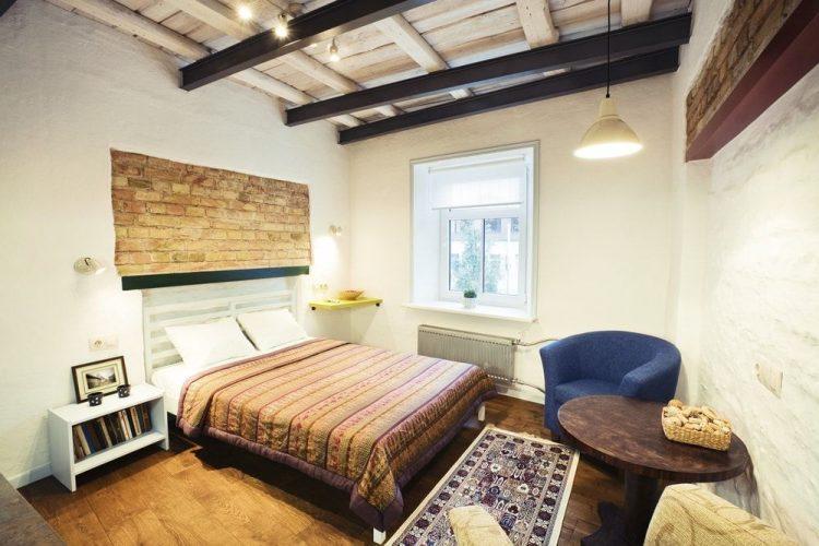 Một phòng ngủ nhỏ theo phong cách Eclectic có sàn gỗ cứng và trần nhà mộc mạc với dầm. Phòng có một chiếc giường ấm cúng và một cặp ghế hiện đại ở bên cạnh, cùng với một bàn cà phê tròn.