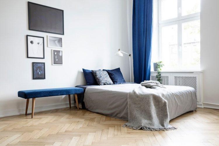 Một phòng ngủ chính rộng rãi chiết trung với những bức tường trắng và sàn gỗ cứng kiểu xương cá. Phòng cũng có tông màu xanh da trời.