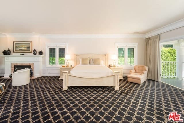 Phòng ngủ chính rộng rãi và sang trọng này có sàn trải thảm hoa văn màu đen làm cho tông màu sáng của chiếc giường ngủ nổi bật.  Điều này tương phản trực tiếp với lớp phủ màu trắng của lò sưởi ở bên cạnh giường nằm trên đỉnh.