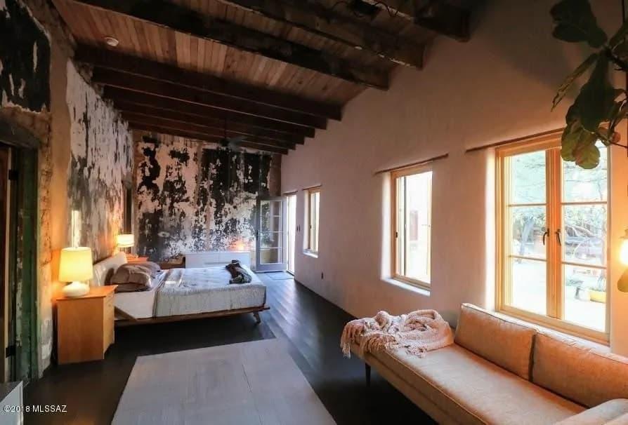 Phòng ngủ mộc mạc này có trần nhà bằng gỗ đẹp với dầm lộ ra ngoài.  Điều này được kết hợp với một bức tường trắng đáng yêu ở một bên và một bức tường đen trắng đau khổ ở bên kia.  Những bức tường này đi hoàn hảo với sàn màu đen làm cho chiếc giường nổi bật.