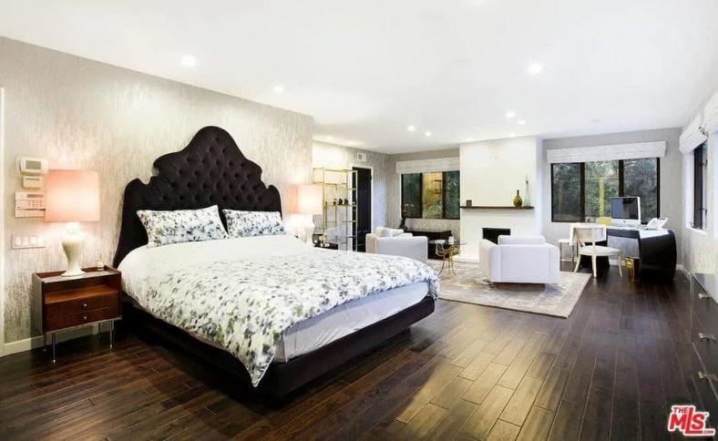 Chiếc giường búi đen tuyệt đẹp nổi bật trên trần nhà trắng sáng với ánh đèn lõm.  Những yếu tố tương phản này được cân bằng bởi sàn gỗ cứng tối màu và bàn cạnh giường màu nâu sẫm phù hợp.