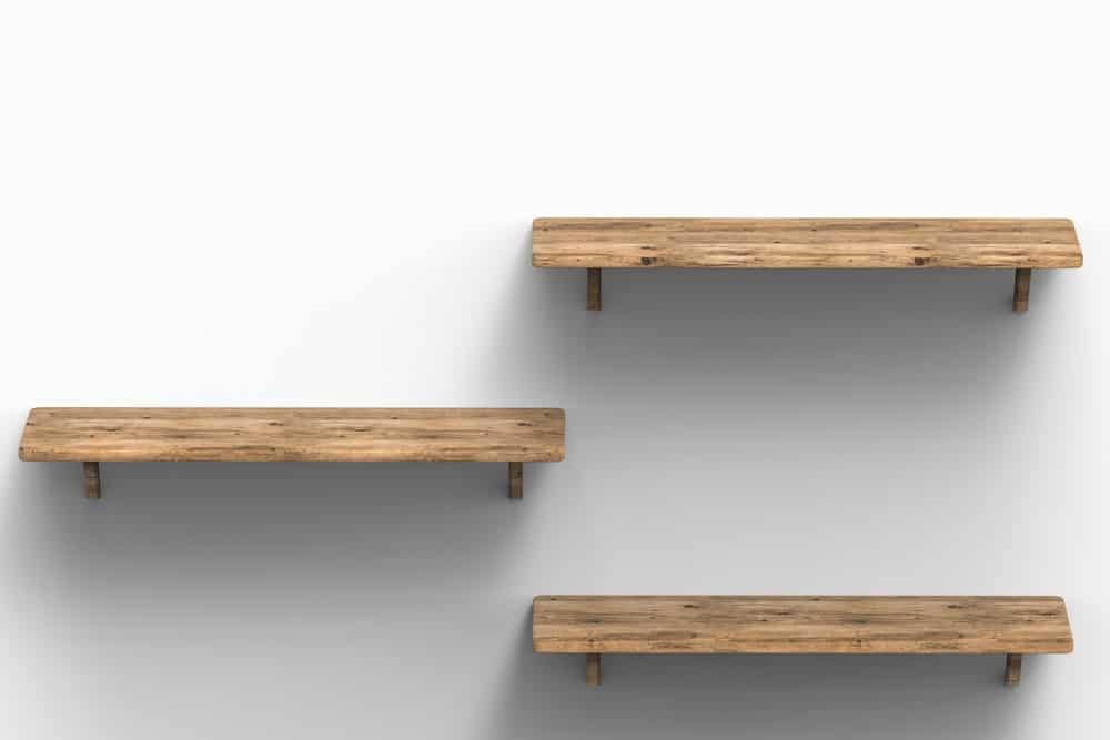 Ba kệ gỗ nổi trên một bức tường trắng.