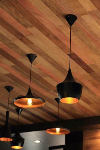 Mặt dây treo màu đen từ trần nhà ốp gỗ.