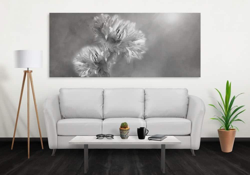 Một phòng khách đơn giản được bổ sung bởi bức tranh lớn của một bông hoa trên bức tường phía trên chiếc ghế dài.