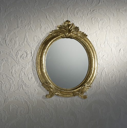 Một gương hình elip đóng khung vàng gắn trên một bức tường kết cấu màu trắng.